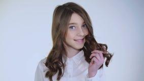 La ragazza abbastanza modesta dei giovani gioca i suoi capelli e sorride alla macchina fotografica archivi video