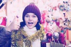 La ragazza abbastanza teenager sceglie le decorazioni floreali Fotografie Stock Libere da Diritti
