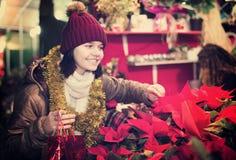 La ragazza abbastanza teenager sceglie le decorazioni floreali Immagine Stock Libera da Diritti