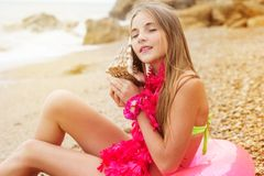 La ragazza abbastanza teenager sta sedendosi sull'anello di gomma con Fotografie Stock