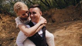 La ragazza abbraccia il suo ragazzo da dietro Preme la sua guancia lui ed ai sorrisi Il tipo sorride indietro Giovani belle coppi video d archivio