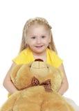 La ragazza abbraccia un grande orsacchiotto Immagini Stock