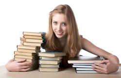 La ragazza abbraccia un mucchio dei libri Immagine Stock