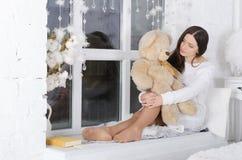 La ragazza abbraccia un orsacchiotto immagine stock