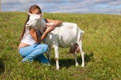 La ragazza abbraccia una capra bianca Fotografia Stock