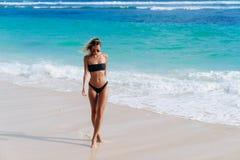 La ragazza abbronzata in costume da bagno ed occhiali da sole neri cammina lungo la riva della spiaggia immagine stock libera da diritti