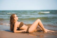 La ragazza abbronzata sexy in un costume da bagno si trova sulla spiaggia Fotografie Stock Libere da Diritti