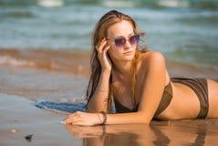 La ragazza abbronzata sexy in un costume da bagno si trova sulla spiaggia Fotografia Stock Libera da Diritti