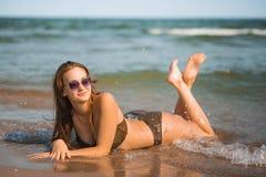 La ragazza abbronzata sexy in un costume da bagno si trova sulla spiaggia Immagini Stock Libere da Diritti