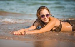 La ragazza abbronzata sexy in un costume da bagno si trova sulla spiaggia Fotografia Stock