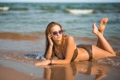 La ragazza abbronzata sexy in un costume da bagno si trova sulla spiaggia Immagini Stock