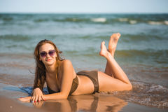La ragazza abbronzata sexy in un costume da bagno si trova sulla spiaggia Fotografie Stock
