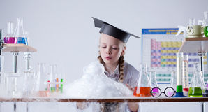La ragazza abile esamina il risultato dell'esperimento chimico Fotografia Stock