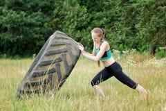 La ragazza in abiti sportivi alza la gomma Allenamento della via Fotografie Stock