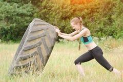 La ragazza in abiti sportivi alza la gomma Allenamento della via Fotografia Stock Libera da Diritti