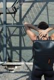 La ragazza accanto alla costruzione con uno zaino nero sulla parte posteriore Immagine Stock