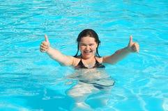 La ragazza in acqua dà il gesto Fotografia Stock