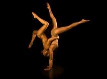 La ragazza acrobatica due ha modificato in oro Immagine Stock