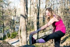 La ragazza adatta allunga la gamba prima di correre nel legno Immagini Stock Libere da Diritti