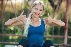 La ragazza adatta in camicia blu e ghette in una palestra del parco mostra il pollice, esaminante la macchina fotografica e sorri fotografia stock