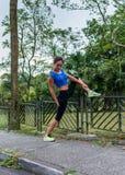 La ragazza adatta che fa allungando l'esercizio sopra recinta il parco Atleta femminile che prepara per l'allenamento di mattina  Fotografia Stock