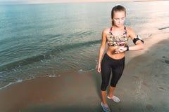La ragazza adatta dei giovani che esamina l'orologio nel corso della mattinata si esercita sull'alba della spiaggia Immagine Stock
