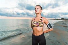 La ragazza adatta dei giovani che fa la mattina si esercita sulla spiaggia all'alba Fotografie Stock Libere da Diritti