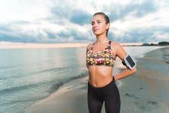 La ragazza adatta dei giovani che fa la mattina si esercita sulla spiaggia all'alba Fotografie Stock