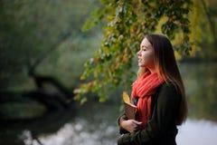 La ragazza adorabile con una sciarpa rossa luminosa cammina nel parco di autunno Immagine Stock
