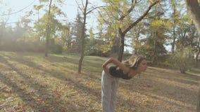 La ragazza adorabile in cuffie fa un allenamento in stock footage