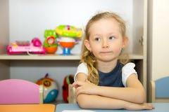 La ragazza adorabile del bambino estrae una spazzola e le pitture nella stanza della scuola materna Bambino nell'asilo nella clas Fotografia Stock