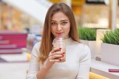La ragazza adorabile esamina la macchina fotografica con l'espressione soddisfatta, bevande munge il cocktail, indossa il saltato fotografie stock libere da diritti