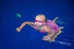 La ragazza adorabile in occhiali da sole nuota da solo in stagno vicino alla scala Immagini Stock