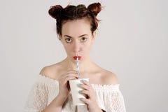 La ragazza adorabile sta bevendo con una paglia con un fronte serio Fotografia Stock Libera da Diritti