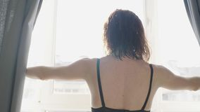 La ragazza adorabile ? sveglia e stante prima della finestra Belle tende di apertura della donna e guardare attraverso la finestr video d archivio