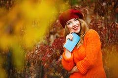 La ragazza adorabile in un berretto e un maglione in autunno parcheggiano, tenendo una n fotografie stock