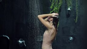 La ragazza adorabile in un bikini rosa prende una doccia fuori della zona della stazione termale, rilassantesi la vacanza stock footage