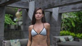 La ragazza adulta snella in costume da bagno che va verso la macchina fotografica, modello cammina fuori stock footage
