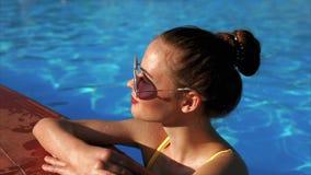 La ragazza adulta sta raffreddandosi nello stagno dopo avere preso il sole su una sedia a sdraio, un'estate video d archivio