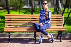 La ragazza affascinante che cammina nel parco e si siede sul banco Immagine Stock Libera da Diritti