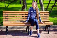 La ragazza affascinante che cammina nel parco e si siede sul banco con gli occhi chiusi Fotografia Stock Libera da Diritti