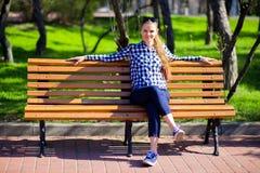 La ragazza affascinante che cammina nel parco e si siede sul banco con gli occhiali da sole Immagine Stock