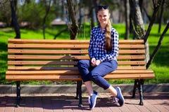 La ragazza affascinante che cammina nel parco e si siede sul banco con gli occhiali da sole Fotografia Stock Libera da Diritti