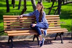 La ragazza affascinante che cammina nel parco e si siede sul banco con gli occhiali da sole Fotografia Stock