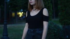 La ragazza affascinante con i capelli di scarsità guarda avanti e camminando giù la via stock footage