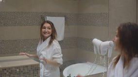 La ragazza affascinante divertente in abito bianco ha preso il bagno e canta davanti allo specchio con hairdryer archivi video
