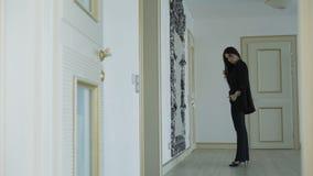 La ragazza affascinante esamina lo specchio e va via nella casa 4K archivi video