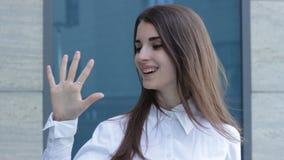 La ragazza affascinante sorride alla macchina fotografica e mostra il gesto cinque archivi video