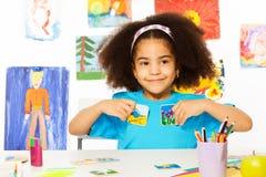 La ragazza africana gioca il gioco inerente allo sviluppo, tiene le carte Fotografia Stock Libera da Diritti