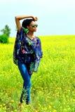 La ragazza afroamericana che indossa gli occhiali da sole sta con le sue mani sul campo con i fiori gialli e distoglie lo sguardo Fotografia Stock